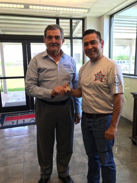 Commissioner Julian Alvarez presents a TWC Challenge Coin to Hondo Director of Economic Development Jesse M. Perez.