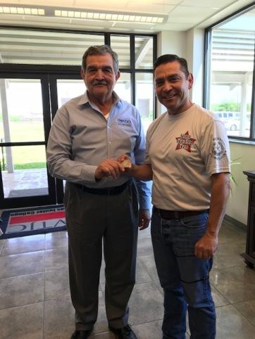 Commissioner Julian Alvarez presents a TWC Challenge Coin to Hondo Director of Economic Development Jesse M. Perez.