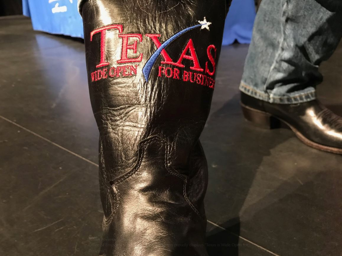 "Director of Employer Initiatives Aaron Demerson proudly displays his ""Texas is Wide Open for Business"" boots."
