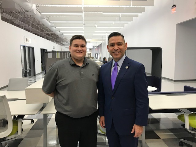 Photo: TWC Commissioner Representing Labor Julian Alvarez (right) and newly hired Booz Allen Hamilton employee Jared Stephens (left) pose for a photograph.