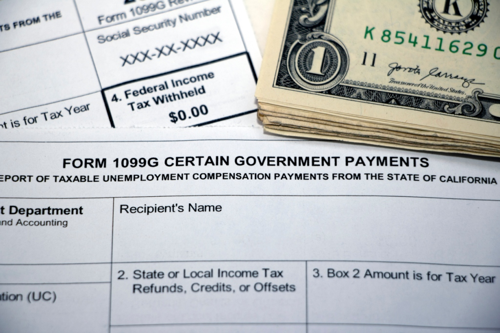 Closeup of overlapping tax forms, Form 1099G Certain Government Payments, Federal Income Tax Withheld $0.00, with stack of cash, blank form boxes.